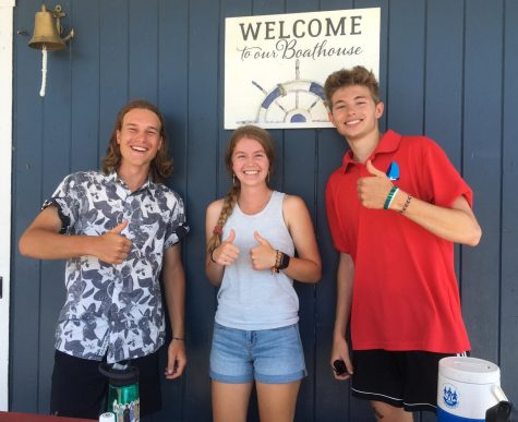Jeffery Wright, Isabelle Koerner, and Nate DeGregorio stand in front of a welcome sign at the boat house at at Hopkinton (Mass.) State Park.