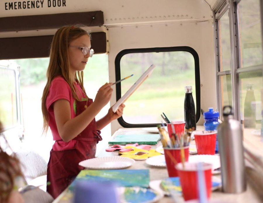 Nine-year-old Skylar paints a canvas to accompany the clay flower she created in a previous session aboard the School Bus Studio.